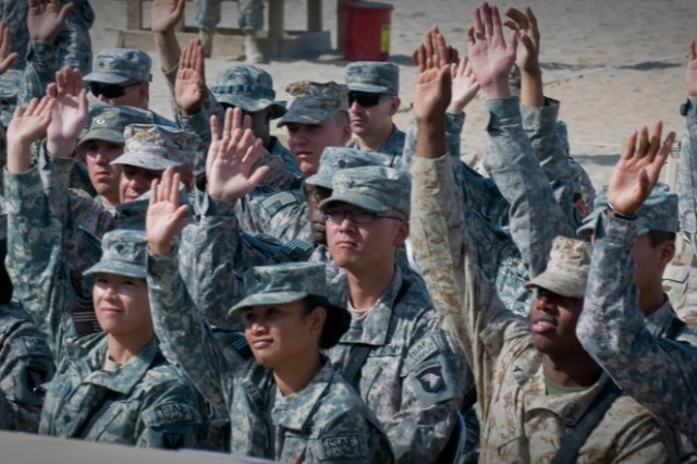Servicemembers from areas of operation around Afghanistan raise their hand in order to signify that they will soon be U.S. citizens during a naturalization ceremony at Kandahar Airfield, Afghanistan, Oct. 1. A total of 88 servicemembers became citizens during the ceremony. The ceremony was the first of its kind held at Kandahar Airfield, an active combat zone.