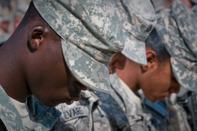 Army Pfc. Olumide Aladesaiye, a native of Nigeria, bows his head during the benediction for the naturalization ceremony at Kandahar Airfield, Afghanistan, Oct. 1. A total of 88 servicemembers were naturalized during the ceremony. The ceremony was the first of its kind held at Kandahar Airfield, an active combat zone.
