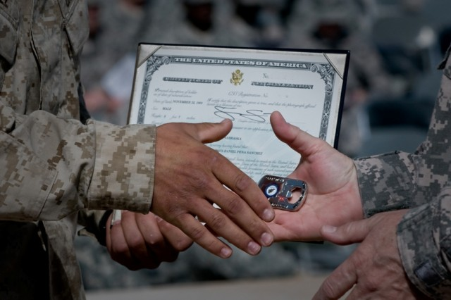 """A U.S. Marine receives his Certificate of Naturalization and a command coin from Army Maj. Gen. Timothy McHale, deputy commander of support for U.S. Forces-Afghanistan, during a naturalization ceremony at Kandahar Airfield, Afghanistan, Oct. 1. A total of 88 servicemembers were naturalized during the ceremony. The ceremony was the first of its kind held at Kandahar Airfield, an active combat zone. """""""