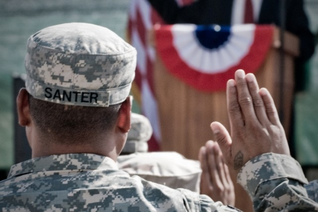 """: Army Sgt. Barvin Santer, a native of Micronesia, raises his right hand while repeating the Oath of Allegiance in order to become a U.S. citizen during a naturalization ceremony at Kandahar Airfield, Afghanistan, Oct. 1. A total of 88 servicemembers were naturalized during the ceremony. The ceremony was the first of its kind held at Kandahar Airfield, an active combat zone."""""""