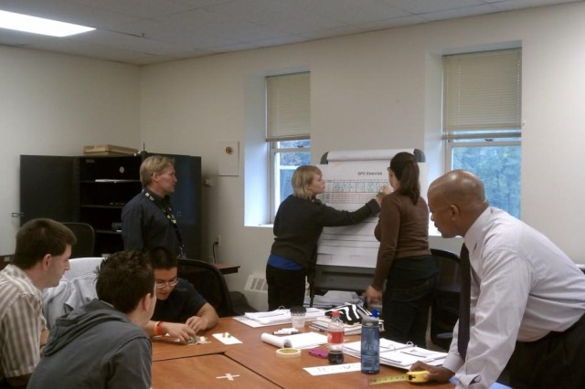 Instructor Edward Borneman reviews a chart as the Lean Six Sigma Black Belt class is engaged in a data gathering exercise at Picatinny Arsenal, N.J. The individuals are (from left to right): Edward Jung , Kevin Caska, George Moreno, Edward Bornemann, Mandy Morrell, Sarah Longo and Gary Barber.
