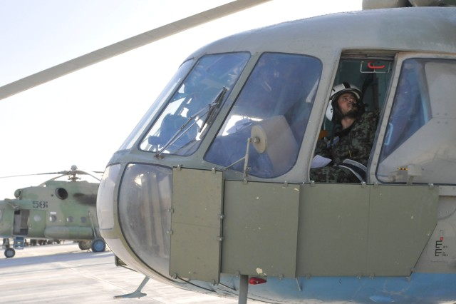 KANDAHAR AIRFIELD, Afghanistan - Abdul Hamed, a helicopter pilot from the Afghanistan National Army Air Corps, 205th Corps, conducts pre-flight checks on an MI-17 helicopter Sept. 22. Afghan and American pilots flew two MI-17 helicopters on a routine troop movement mission to several forward operating bases throughout the southern part of Afghanistan in support of Operation Enduring Freedom.