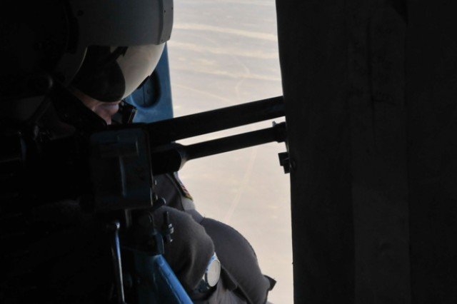 KANDAHAR AIRFIELD, Afghanistan - U.S. Air Force Tech. Sgt. Frank Dirr, a Victoria, Texas, native and a crew chief with the 442nd Air Expeditionary Advisory Squadron, looks out the window of an MI-17 helicopter Sept. 22. Afghan and American pilots flew two MI-17 helicopters on a routine troop movement mission to several forward operating bases throughout the southern part of Afghanistan in support of Operation Enduring Freedom.