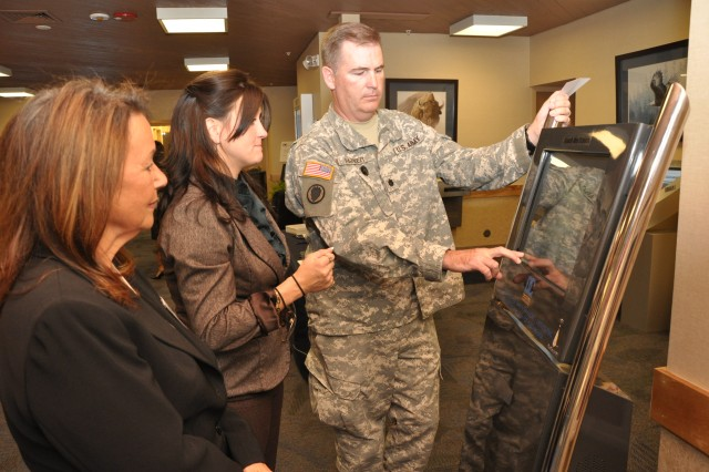 FORT CARSON, Colo.- From left, Elsa Killeen, senior vice president, and Tiffany Membery, regional sales manager, PacRim Digital Media Group, and  Lt. Col. Daniel Parker, deputy brigade commander, 43rd Sustainment Brigade, test out the interactive Warrior Family Community Partnership information kiosk at The Hub Sept. 24.