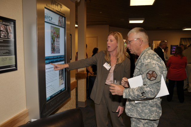 FORT CARSON, Colo.- Kristen Kea, Warrior Family Community Partnership manager, and Chap. (Lt. Col.) David M. Brown, deputy garrison chaplain, look at the digital information sign at the WFCP in The Hub Sept. 24.