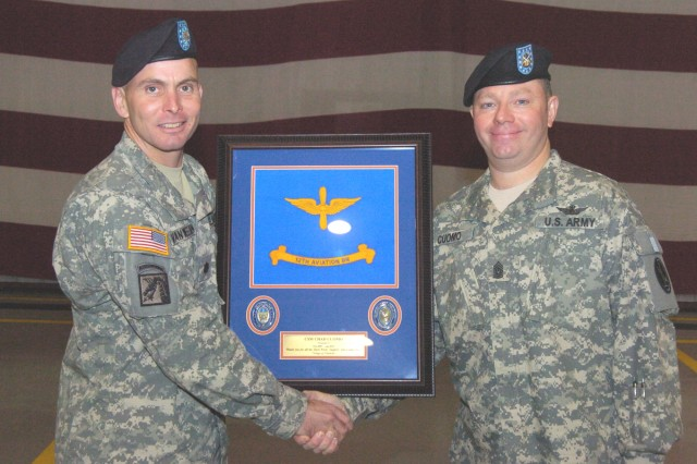Command Sgt. Maj. Chad Cuomo receives a memento and hand shake for his service from 12th  Battalion Commander Lt. Col. Douglas VanWeelden.  Cuomo was replaced at the battalion by Command Sgt. Maj. William Yeargan, and now serves as the new Command Sgt. Maj. at headquarters, Army Air Operations Group on Fort McNair, D.C.