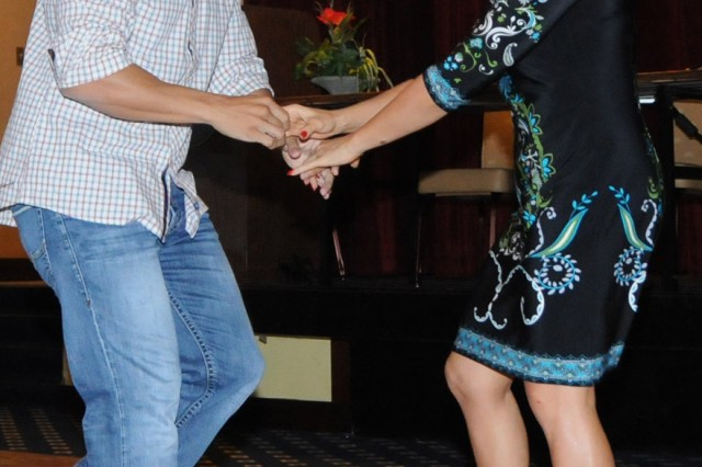 Capt. Roger Garcia, B Co., 1st Bn., 145th Avn. Regt., and Marta Trevathan, Hispanic Dance instructor here, participate in the first Hispanic Dance Night.