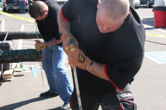 FORT CARSON, Colo.- Spc. Robert Hutchins, front, 549th Quartermaster Company, 68th Combat Sustainment Support Battalion, 43rd Sustainment Brigade, and Adam Miller, Family member, compete in the log sawing contest Saturday at Oktoberfest.