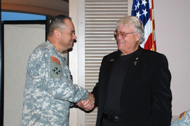 Col. Jim Lee, 470th Military Intelligence Brigade commander, presents a challenge coin to Vietnam veteran David Roever following his welcome Sept. 20 at the Fort Sam Houston Golf Club.