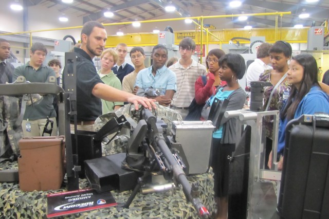 Greg Stuhr, a general engineer at the Prototype Integration Facility, shows students from Sparkman High School the new technologies added to a M240 mounted rifle used on Chinook and Black Hawk helicopters. The students were among about 350 11th-graders from area high schools who participated in the annual Adventures in Engineering at Redstone Arsenal.""