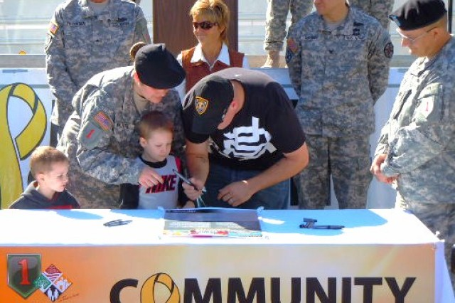 A Soldier with the Combat Aviation Brigade, 1st Infantry Division, and her Family sign the Army Community Covenant with Pottawatomie County during OZToberfest Oct. 3 in Wamego, Kan.