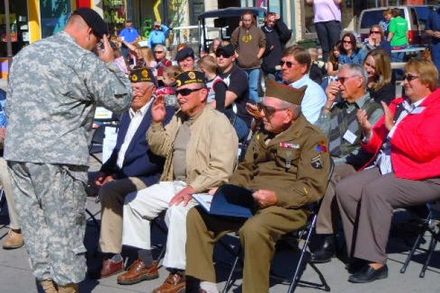 Lt. Col. Erich Campbell, commander of the Combat Aviation Brigade rear-detachment, 1st Infantry Division, salutes a local veteran during an Army Community Covenant re-signing Oct. 3, in which the CAB reaffirmed its partnership with Pottawatomie County in a formal ceremony during the final days of OZToberfest in Wamego, Kan.