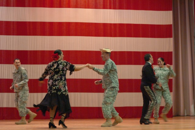 Fort Bliss Command Sgt. Maj. David Davenport dances the salsa on stage with a partner at the Hispanic American Heritage Month observance held at Soldier Hall Oct. 7.