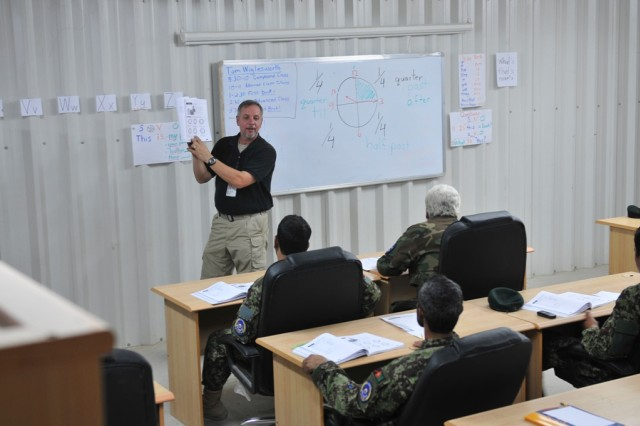 KANDAHAR AIRFIELD, Afghanistan - Tom Wiglesworth, a native of Columbia, S.C., and English teacher with the Department of Defense Education Activity, goes over a lesson with his class Sept. 30. Afghan airmen of the Kandahar Air Wing take part in a program designed to improve their English to better communicate with coalition forces. ""