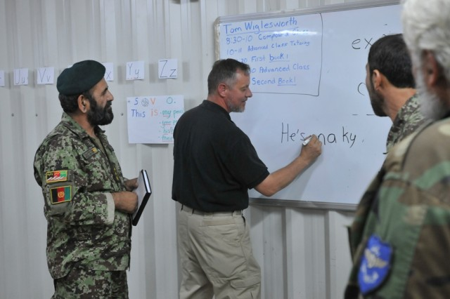 Tom Wiglesworth, (center) a native of Columbia, S.C., and English teacher with the Department of Defense Education Activity, talks to his students after class Sept. 30. Afghan airmen of the Kandahar Air Wing take classes designed to improve their English to better communicate with coalition forces.""