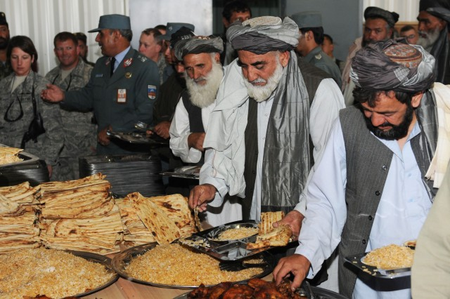 Afghan elders, security forces and Coalition Forces enjoy a meal