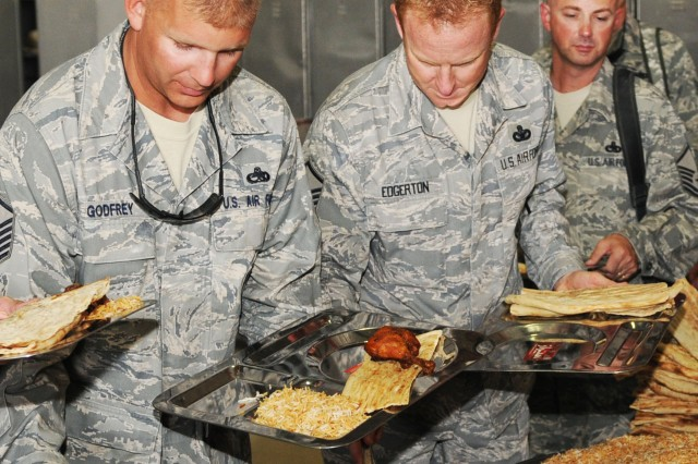 U.S. Airmen enjoy an array of Afghan cuisine following a ceremony that celebrated the first year anniversary of the Kandahar Air Wing at Kandahar Airfield, Afghanistan, Oct. 5.