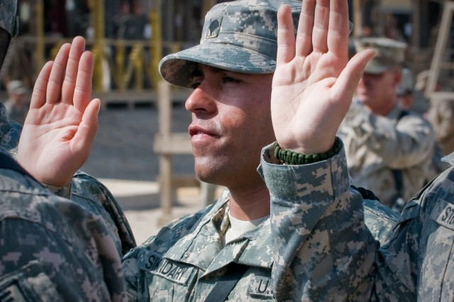 Army Spc. Hamed Sikandary, a native of Afghanistan, raises his right hand while repeating the Oath of Allegiance in order to become a U.S. citizen during a naturalization ceremony at Kandahar Airfield, Afghanistan, Oct. 1. A total of 88 servicemembers were naturalized during the ceremony. The ceremony was the first of its kind held at Kandahar Airfield, said a U.S. Department of Homeland Security official.
