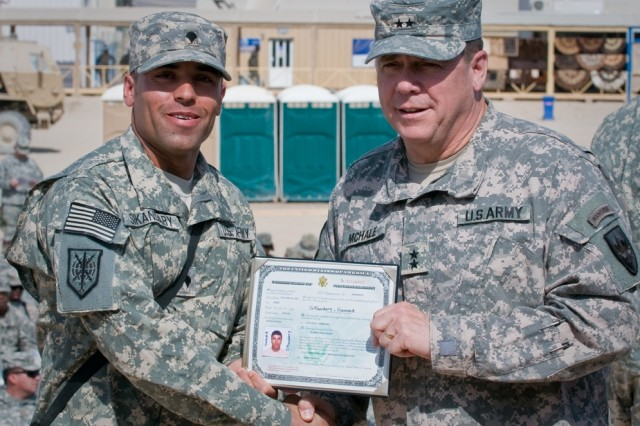 Army Spc. Hamed Sikandary, a native of Afghanistan, receives his Certificate of Naturalization and a command coin from Army Maj. Gen. Timothy McHale, deputy commander of support for U.S. Forces-Afghanistan, during a naturalization ceremony at Kandahar Airfield, Afghanistan, Oct. 1. A total of 88 servicemembers were naturalized during the ceremony. The ceremony was the first of its kind held at Kandahar Airfield, said a U.S. Department of Homeland Security official.