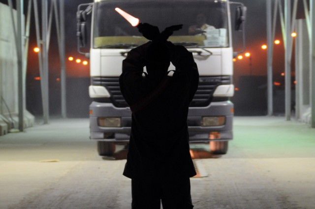 A security guard guides a truck in to the searching lane for inspection at a U.S. base near Nasiriyah Sept. 20.