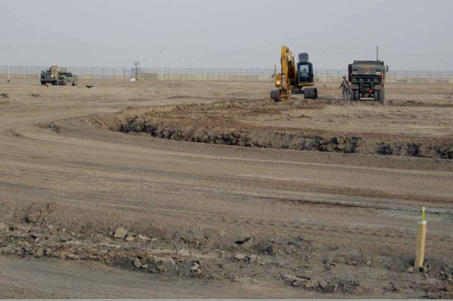 Soldiers with 328th Engineer Support Company, 36th Engineer Brigade dig a drainage ditch alongside the road using an excavator at what is now an overflow parking lot for entry control point 5 at Contingency Operating Base Adder, Iraq.