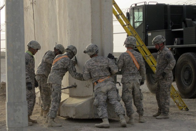Soldiers with 1st Platoon, 328th Engineer Support Company, 36th Engineer Brigade, tell the crane operator what they need him to do in order to place the T-wall as they build Safe Haven, an overflow parking lot for entry control point 5 at Contingency Operating Base Adder, Iraq.