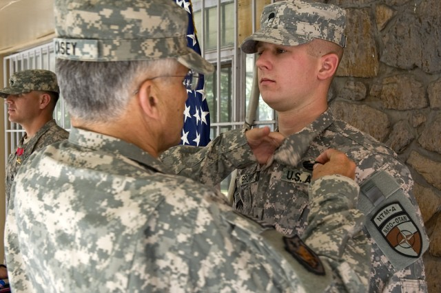KABUL, Afghanistan- Gen. George W. Casey, Chief of Staff of the US Army, presents the combat action badge to Army Specialist Garland Brown III Oct. 11, 2010. Brown received the badge for his actions after receiving indirect and small arms fire on Sept. 26, 2010.