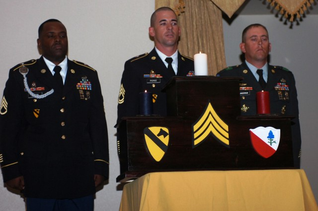 FORT HOOD, Texas- (From left to right) Staff Sgt. Gregory Brown, Sgt. 1st Class Kenneth Pierce, and Sgt. 1st Class Robert Clingerman, all with the 15th Brigade Support Battalion, 2nd Brigade Combat Team, 1st Cavalry Division, stand in front of candles during the 15th BSB's NCO Induction Ceremony in the Club Hood Ballroom, here, Oct. 7.  Each NCO said a few words pertaining to the history of the NCO corps, and then each of them lit a different colored candle representing an individual distinction of the NCO Creed.