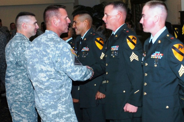 FORT HOOD, Texas- Col. John Peeler (center left), commander of the 2nd Brigade Combat Team, 1st Cavalry Division, and Lt. Col. Matthew Ruedi (far left), commander for the 15th Brigade Support Battalion, 2nd BCT, congratulate new sergeants from the 15th BSB after being inducted into the Noncommissioned Officer Corps during the 15th BSB's NCO Induction Ceremony in the Club Hood Ballroom, Oct. 7.  The ceremony acts as a 'Rite of Passage' for the new sergeants.