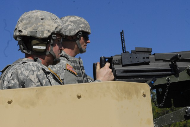 Staff Sgt. Micheal Mitchell, left, fires the MK19 40mm grenade machine gun Monday from the top of a Humvee at Ruth Range. At right is his spotter, Pfc. David Behrend. The two were among 10 Soldiers from B Company, 2nd Battalion, 29th Infantry Regiment, who took part in the Maneuver Battle Lab's weeklong experiment on a modified rear sight for the weapon, which also is pictured. Officials said the new design could lower manufacturing and maintenance costs.