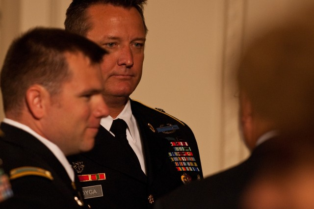 Master Sergeant Jim Lodyga listens to past Medal of Honor recipients, while Major Robert Cusick stands next to him on Wednesday, Oct 6, 2010, at the White House ceremony in Washington to honor Staff Sergeant Robert Miller, their fellow team member. Miller was awarded the Medal of Honor posthumously for his actions in Afghanistan in 2008.