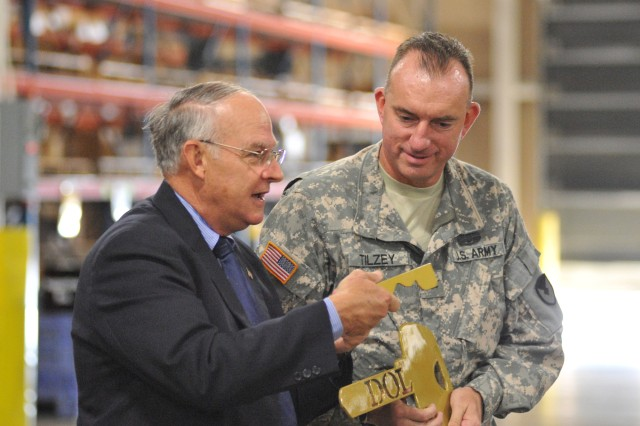 Bob Bishop, director of Logistics, gives ceremonial keys to Col. Danny Tilzey, 407th AFSB commander, during a transfer of control ceremony, taking Fort Hood's Directorate of Logistics from Installation Management Command to the Army Sustainment Command's 407th Army Field Support Brigade, in a ceremony Oct. 8 at a DOL warehouse.