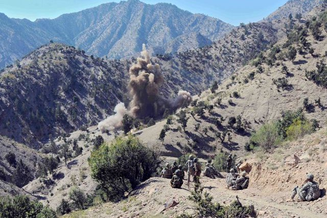 Soldiers assigned to Troop A,  1st Squadron, 33rd Cavalry Regiment watch as explosives detonate inside an insurgent weapons cache during a joint air-assault mission with Afghan National Security Forces in the mountains of Khowst Province Oct. 8.
