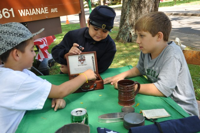 """Two young boys play an old coin game played by Soldiers during the Civil War as part of a demonstration during the """"Living History Day"""" at the """"Tropic Lightning Museum"""" on Schofield Barracks, Hawaii, Oct. 8. During the event, visitors were allowed hands- on tours of many of the museum's military artifacts and treasures. (U.S. Army photo by Sgt. Jesus J. Aranda, 25th Infantry Division Public Affairs Office)"""