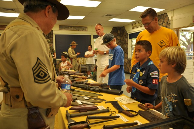 """A group of children and parents examine authentic military weaponry during the """"Living History Day"""" at the """"Tropic Lightning Museum"""" on Schofield Barracks, Hawaii, Oct. 8. During the event, visitors were allowed hands-on tours of many of the museum's military artifacts and treasures with historic facts and stories taught by military re-enactors. (U.S. Army photo by Sgt. Jesus J. Aranda, 25th Infantry Division Public Affairs Office)"""