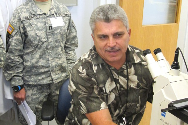 Chief leishmaniasis researcher, Juan Mendez, prepares a slide for U.S. Army Africa Capt. Gabrielle Caldara to view during Tropical Medicine Course (TMC) training Sept. 13, 2010, at Walter Reed Army Institute of Research in Silver Spring, Md.