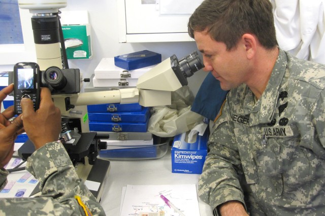 Sgt. 1st Class Roddy Rieger, U.S. Army Africa Command Surgeon NCOIC, views leishmaniasis under the microscope during Tropical Medicine Course (TMC) training Sept. 13, 2010, at Walter Reed Army Institute of Research in Silver Spring, Md.