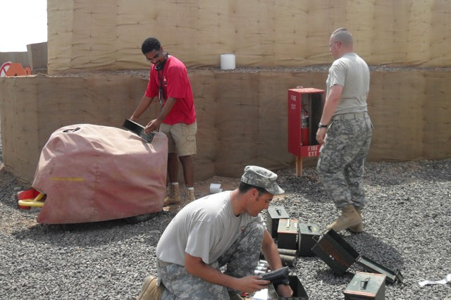 Contractor Ramon Barboa (left to right), Sgt. 1st Class Luis Febles, and Staff Sgt. Shawn Moldenhauer inspect munitions at Camp Lemonnier, Djibouti.