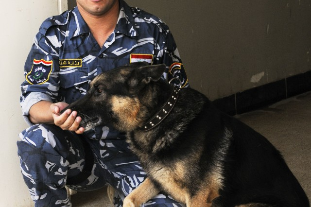"BAGHDAD Aca,!"" A Canine Handler School student shares a little down time with his partner, an explosive-detection dog, at the Baghdad Police College Oct. 6."