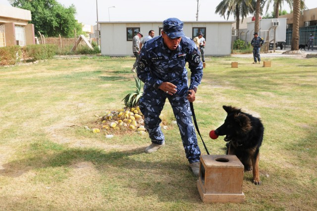 "BAGHDAD Aca,!"" A Canine Handler School student rewards an explosive-detection dog during a training exercise at the Baghdad Police College Oct. 6."