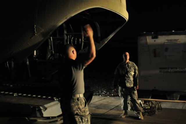 Spc. Robert Eayre, A Company, Task Force Troubleshooter Movement Control Team pax runner, assists the forklift driver and CH-47 Chinook helicopter crew chiefs load cargo Sept. 30 in preparation for a night mission transporting both cargo and passengers from Kandahar Airfield, to an outlying forward arming and refueling point.