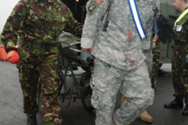 Medics from the 212th Combat Support Hospital and the United Kingdom's 208th Field Hospital (Liverpool), rush a simulated casualty into the hospital as a part of a mass casualty scenario during Operation Starlight, a joint medical training exercise at the Joint Multinational Readiness Center in Hohenfels, Oct 6.