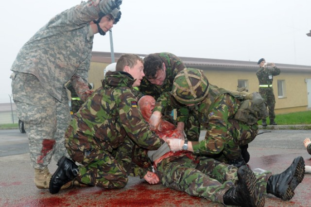 Sgt. Joshua Thompson, of the 212th Combat Support Hospital, directs medics from the United Kingdom's 208th Field Hospital (Liverpool), as they treat a simulated patient during a mass casualty exercise Oct 6. The training was a part of Operation Starlight, a joint medical training exercise at the Joint Multinational Readiness Center in Hohenfels.