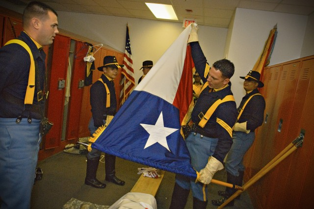 """RANGERS BALLPARK, Arlington Texas- 1st Cavalry Division Honor Guard's non commissioned officer inc,  Sgt. Gregory Bonine (right), of San Diego, Calif., prepares the Texas state flag to be """"posted"""" during  the National Anthem before the start of the American League Divisional Playoff Series, between the Texas Rangers, and the Tampa Bay Rays, Oct. 10."""