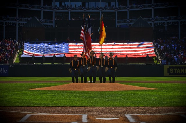 """RANGERS BALLPARK, Arlington Texas -The 1st Cavalry Division Honor Guard """"posts"""" the nations colors behind the pitcher's mound of Rangers Ballpark, Oct. 10, while 20 members of """"America's First Team"""" unfurl Old Glory in center field before Game Four of the American League Championship Series, here."""