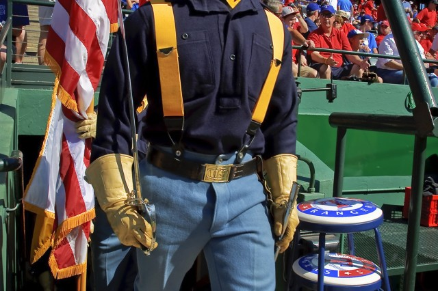 RANGERS BALLPARK, Arlington Texas - Lead Saber, Spc. Josh Merrell, of Battle Creek, Mich., marches the 1st Cavalry Division Honor Guard out of the dugout at Ranger's Ballpark to display the national colors at Game Four of the American League Championship Series, Oct. 10.