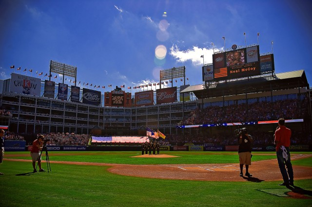 """RANGERS BALLPARK, Arlington Texas — Country music superstar Neal McCoy performs the national anthem prior to Game Four of the American League Divisional Series, here, Oct. 10, as the 1st Cavalry Division Honor Guard and 20 others from """"America's First Team"""" present the nations colors."""
