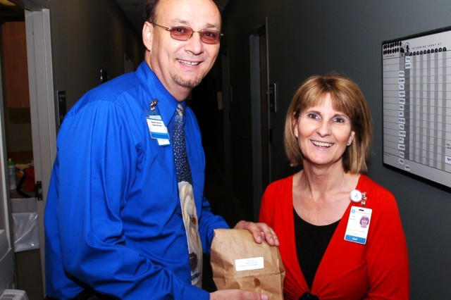 FORT HOOD, Texas - Dennis Horsch, administrator for the William R. Courtney Texas State Veterans Home, Temple, Texas, hands his wife Vickie a bag with breakfast tacos made by Soldiers from Headquarters and Headquarters Company, 2nd Brigade Combat Team, 1st Cavalry Division, during a fundraising event at the WRC Texas State Veterans Home, in Temple, Texas, Oct. 12.