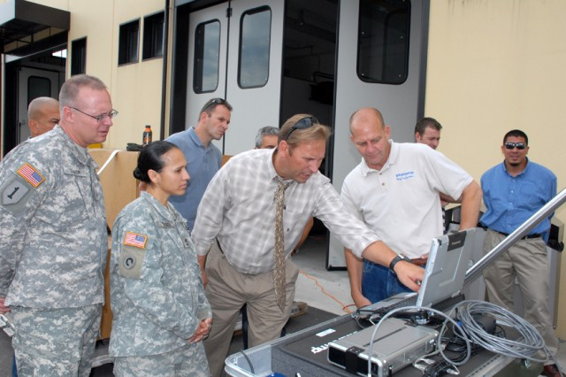 Chief Warrant Officer 2 Terry Throm (left to right), U.S. Army Africa G-4 Mobility Warrant Officer, Sgt. 1st Class Marina Dennis, and Greg Hutcheson, U.S. Army Garrison Directorate of Logisitics, examine Deployable Automated Cargo Measurement System digital measurement euqipment during training at Caserma Ederle, Vicenza, Italy.