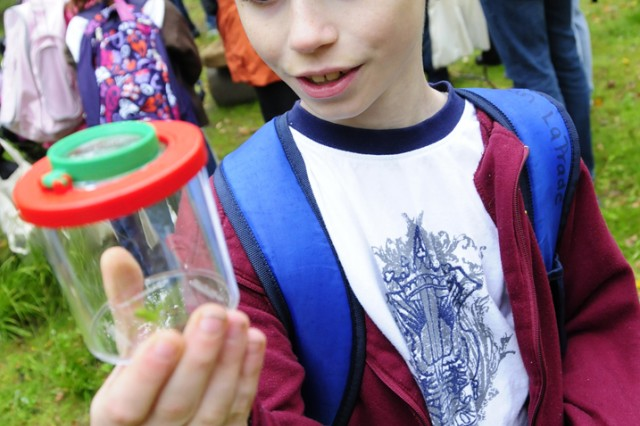 GRAFENWOEHR, Germany - Third-grader Jonathon LaPrade inspects a spider found along the environmental trail in the training area.